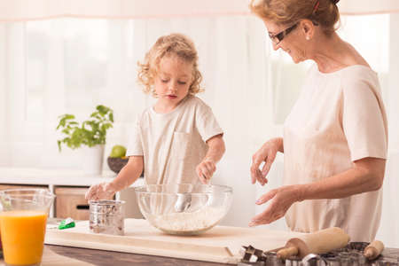 stiring: Young boy stiring the cake ingredients in a bowl with his nanny standing close