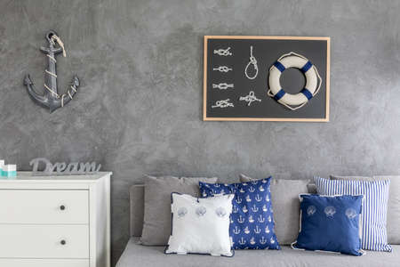 room decoration: Modern flat with nautical decorations, sofa with pattern pillows and white commode