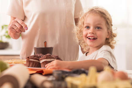 willing: Happy and smiling child willing to eat the muffin from the kitchen worktop Stock Photo