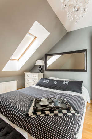 amenities: Bedroom interior with a marital bed, mirror on the wall, roofwindow and stylish chandelier