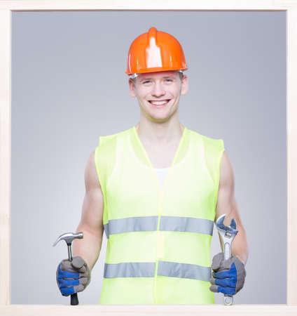 obrero: trabajador sonreído en el chaleco reflectante y healmet en la cabeza, manteniendo las herramientas Foto de archivo