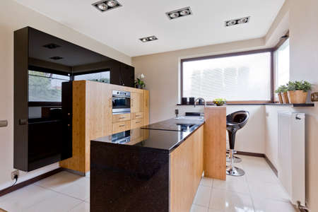 gloss: Spacious villa kitchen with window and modern furniture Stock Photo