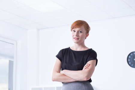 communicative: Young, red haired woman standing in the bright interior with her arms folded