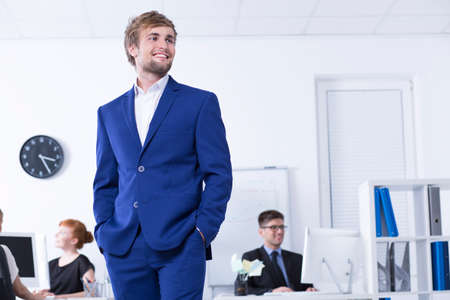 communicative: Young man in blue suit standing in the open space office area Stock Photo
