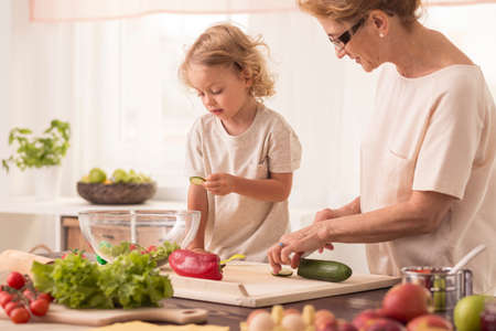 Kitchen interior with senior nanny cooking with the child