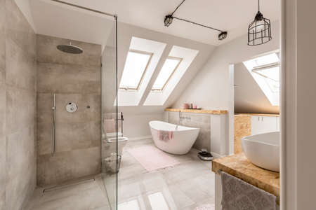 amenities: Modern bathroom interior with minimalistic shower and lighting, white toilet, sink, bathtub and roofwindows Stock Photo