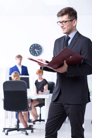 communicative: Elegant man reading the documents with other employees at the background Stock Photo
