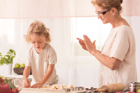 grand child: Senior nanny looking at the child making cookies on the kitchen worktop Stock Photo