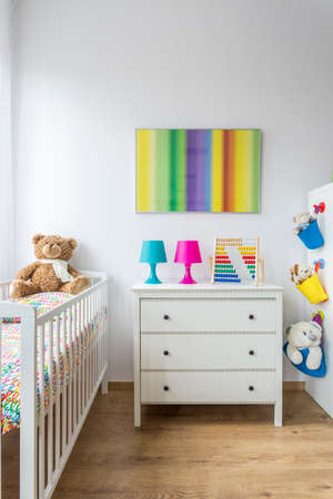 adorable child: Bright adorable child room with cradle and chest of drawers
