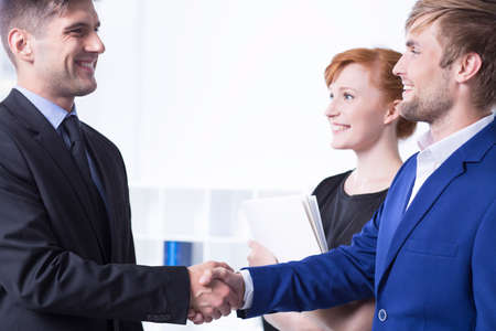 Elegant and smiled man shaking his employee's hand