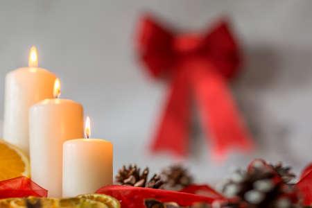 velas de navidad: velas de navidad blancos y cinta roja que cuelga en la pared