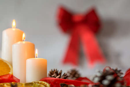 christmas candles: White christmas candles and red ribbon hanging on the wall Stock Photo