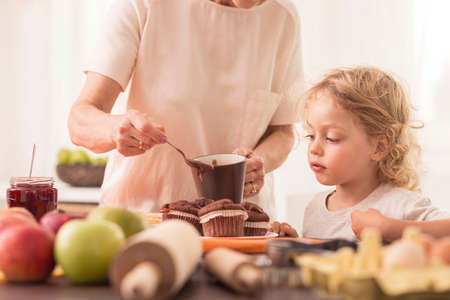 grand child: Young boy looking at the muffins made by his grandma Stock Photo