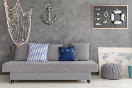 living style: New design grey home interior with nautical decorations, sofa and small pouf