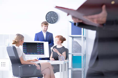 communicative: Elegant  office employees sitting at the work station and talking