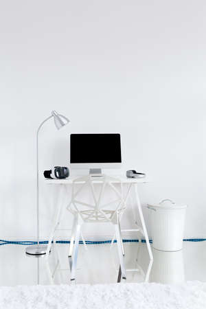 amenities: Home work station with computer on a desk, lamp and modern chair Stock Photo