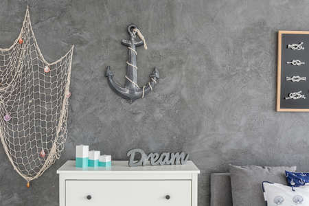 ocean fishing: Modern ocean inspired  interior with white commode, fishing net and anchor hanging on the wall