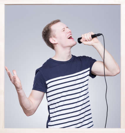 audition: Young man keeping the microphone in his hand and singing Stock Photo