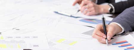Panoramisch beeld van een bureau vol documenten en zakenvrouwen die aantekeningen maken