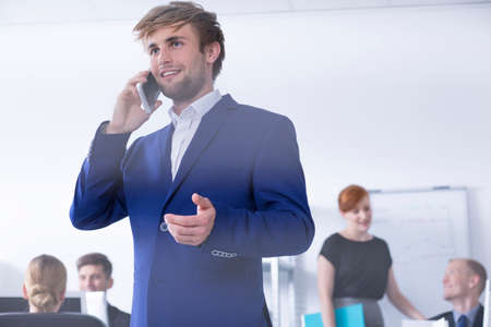 communicative: Closer shot of a man in suit talking on the phone at the office