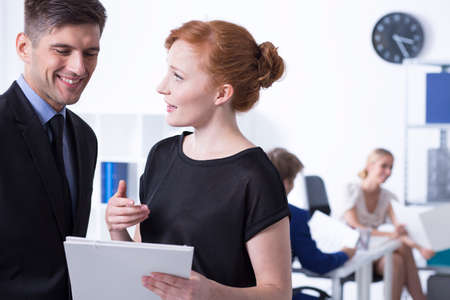 communicative: Red haired woman keeping the documents and talking to her smiled boss Stock Photo