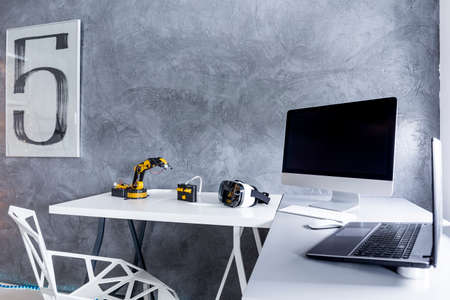 office wall: White desktop with monitor screen, laptop and electronic robots on it Stock Photo