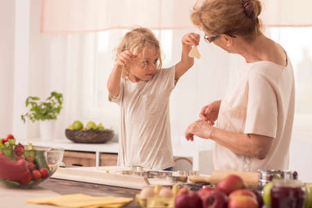 nanny: Young kid showing the various shaped cookies to his nanny