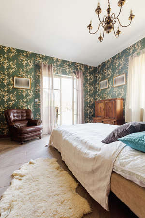 comfort room: Stylish patterned wallpaper bedroom interior and comfortable leather armchair