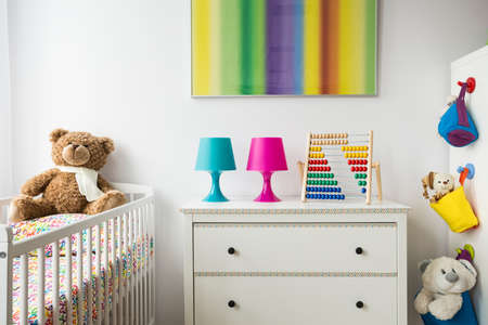 bright paintings: Part of a adorable child room with cradle, chest of drawers and colorful painting