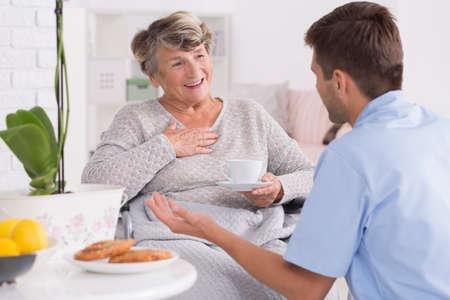 Parlez entre la vieille femme sourit et son jeune infirmier