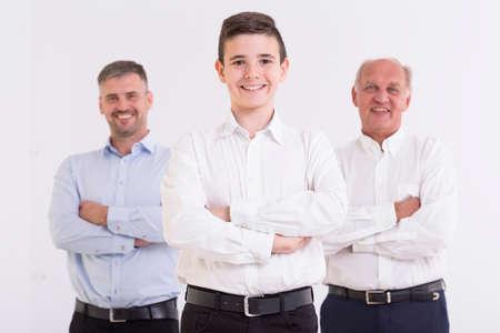 Drie generaties van de mannen die met gevouwen armen en glimlachend