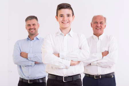 Three generations of men standing with folded arms and smiling