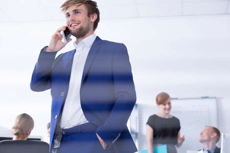 communicative: Elegant and handsome man talking on the phone in open space working area
