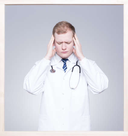 medical occupation: Young doctor touching his head and feeling a terrible headache Stock Photo
