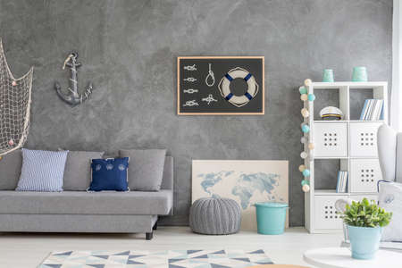 Grey home interior with nautical wall decor, sofa, carpet and white storage unit