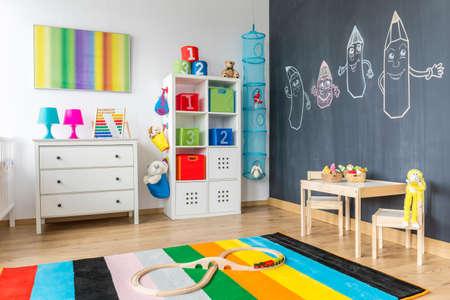 View of kinderkamer met kleurrijke tapijt en bord muur