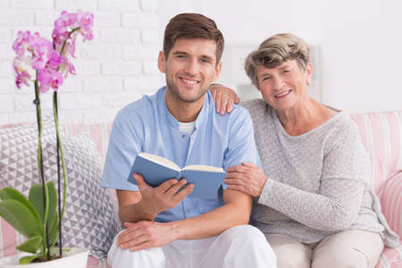 home keeping: Male nurse sitting on a couch close to elder woman and with a book in his hands