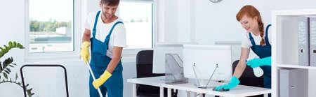 若い女の子からコンピューターと人間、床を拭くことのほこりをクリーニング 写真素材
