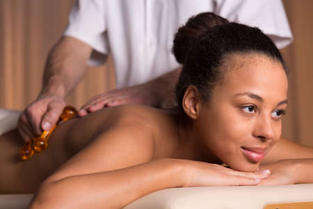relief: Afroamerican woman having back massage in beauty salon