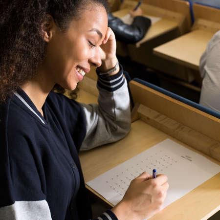 Primer plano de estudiante feliz escribiendo examen fácil Foto de archivo - 65424459