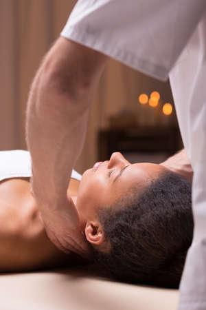 afroamerican: Masseur massaging beautiful afroamerican woman in a spa studio