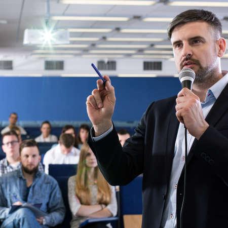 profesor académico hablando con sus estudiantes en la sala de conferencias