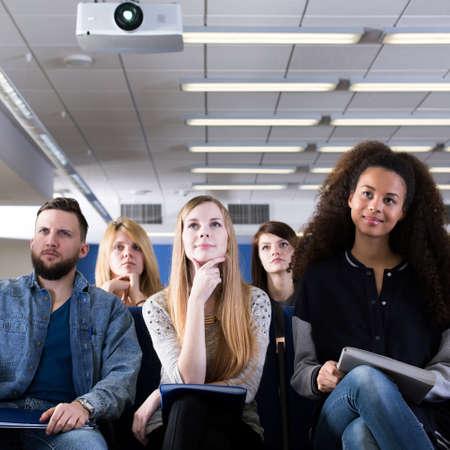 Grupo de estudiantes que se sientan en la sala de conferencias