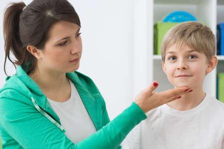 body posture: Young female physiotherapist correcting boys body posture Stock Photo