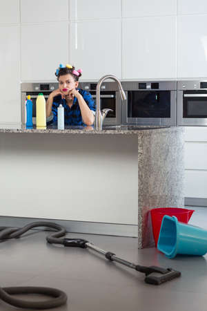 pedantic: Sad woman with hair rollers sitting bored in a beautiful kitchen Stock Photo