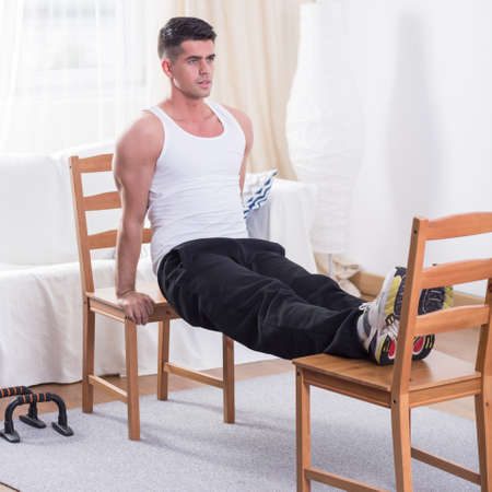 Young man doing his physical training at his flat using the chairs