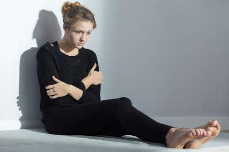 fille triste: Sad girl de porter des vêtements noirs assis sur un plancher