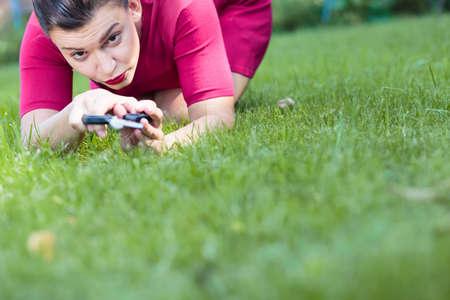 pedantic: Beautiful woman cutting a grass using a scissors