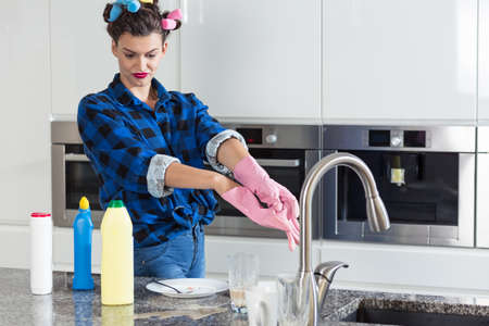 hair rollers: Unhappy woman with a hair rollers cleaning big kitchen