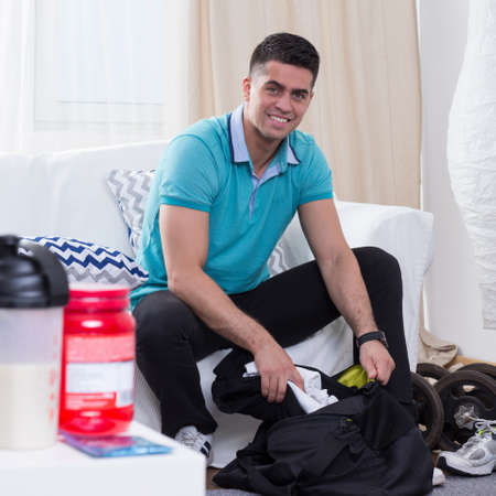 nourish: Smiled man sitting on a couch and preparing himself for the training in the gym